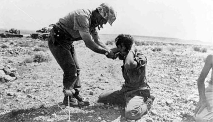 Ο Τούρκος στρατιώτης δίνει τσιγάρο στον αιχμάλωτο Κύπριο στρατιώτη. Μια σπάνια φωτογραφία η οποία δεν φαίνεται να εντάσσεται στο πλαίσιο της προπαγάνδας, αλλά να είναι πραγματική