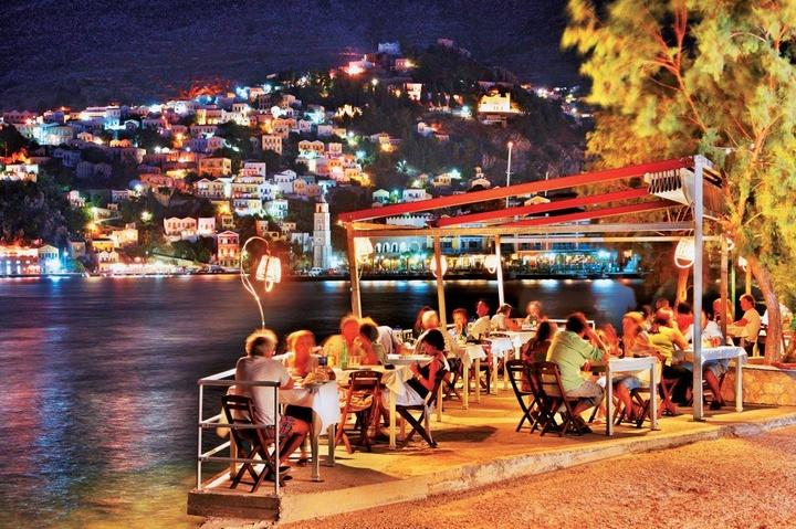 Το βράδυ στο νησί η ζέστη υποχωρεί. Και τότε το ευχαριστιέσαι! Η Σύμη έχει καλό φαγητό. Το απαιτούν οι τουρίστες. Οι εστιάτορες τους ρωτάνε κι αν δεν τους αρέσει κάτι, το λένε στα ίσια – το άκουσα να συμβαίνει αρκετές φορές. Βέβαια πληρώνουν τιμές Αθήνας