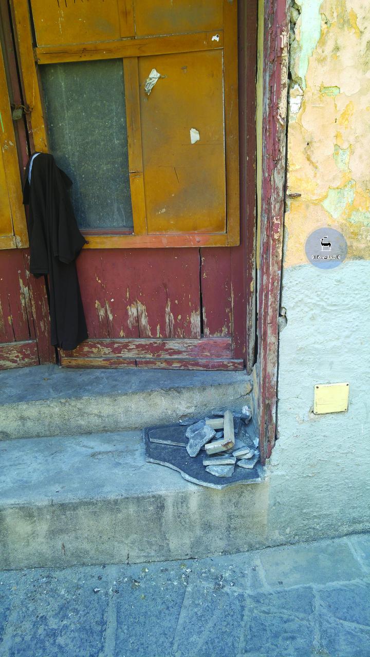 Σπασμένες πλάκες τοποθετημένες μπροστά από ένα εγκαταλελειμμένο κτίριο