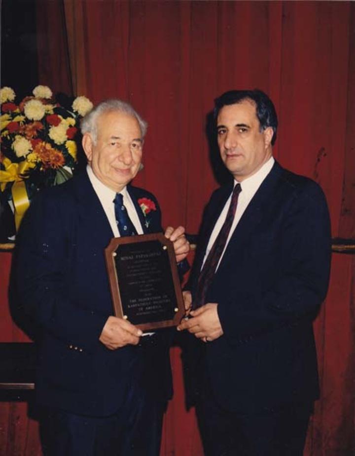 Ο Γιάννης Σακελλάρης, πρόεδρος της Καρπαθιακής Ομοσπονδίας, απονέμει τιμητική πλακέτα στον φιλάνθρωπο Μηνά Παπακώστα