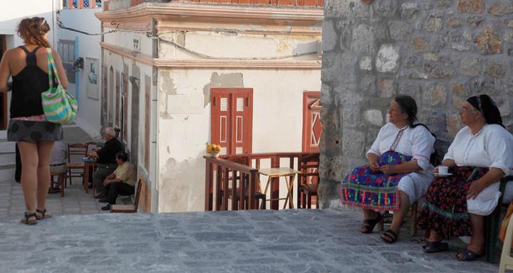 Γυναίκες με παραδοσιακή στολή παρακολουθούν μια τουρίστρια σε στιγμιότυπο από την πλατεία του γραφικού χωριού «Όλυμπος» στην Κάρπαθο                                     (EUROKINISSI / ΧΑΣΙΑΛΗΣ ΒΑΪΟΣ)